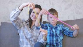 Het gelukkige mamma en de zoon spelen met slijmzitting op de bank Uitrekkend slijm stock videobeelden