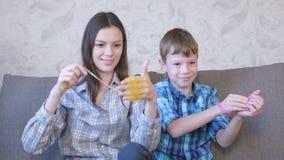 Het gelukkige mamma en de zoon spelen met slijmzitting op de bank Uitrekkend slijm stock footage