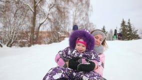 Het gelukkige mamma en dochter sledding in de winter in sneeuw en het spelen sneeuwballen moeder en kind de lach en verheugt zich stock video