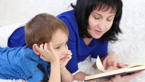 Het gelukkige mamma en haar kind lezen een boek liggend op een witte bank stock videobeelden