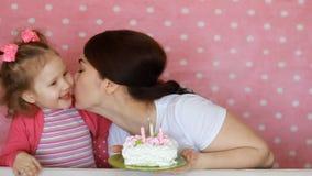 Het gelukkige mamma en het kind maken een wens en slagen kaarsen op verjaardag op bij partij koeken De moeder wenst geluk, omhels stock videobeelden