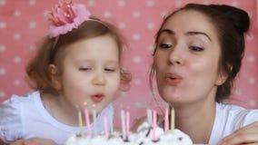Het gelukkige mamma en het kind maken een wens en slagen kaarsen op verjaardag op bij partij koeken De moeder wenst geluk, omhels stock footage