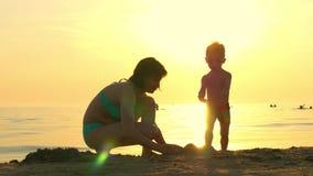 Het gelukkige mamma en kind spelen op het strand in het zand Het mamma en het kind bouwen een zandkasteel tegen de achtergrond va Stock Afbeelding