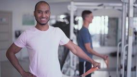 Het gelukkige mannetje is toenemend gewicht gemakkelijk met één hand in de gymnastiekmensen in de Therapie van de gymnastiekgesch stock videobeelden