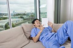 Het gelukkige medio volwassen boek van de mensenlezing terwijl het liggen op bank door venster Stock Foto's