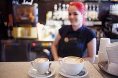 Het gelukkige meisje Barista geeft koffie aan de klanten royalty-vrije stock afbeeldingen