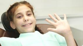 Het gelukkige meisje bekijkt de camera en gelukkig de golven haar hand stock foto's