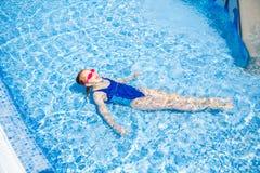 Het gelukkige meisje in beschermende brillen zwemt hierboven in zwembadweergeven van stock fotografie