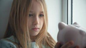 Het gelukkige meisje bespaart geld in spaarvarken in haar huis Kind die een muntstuk opnemen in een spaarvarken, binnen financiee stock video
