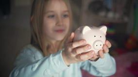 Het gelukkige meisje bespaart geld in spaarvarken in haar huis Kind die een muntstuk opnemen in een spaarvarken, binnen financiee stock footage