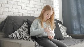 Het gelukkige meisje bespaart geld in spaarvarken in haar huis Kind die een muntstuk opnemen in een spaarvarken, binnen financiee stock videobeelden