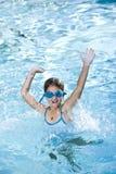 Het gelukkige meisje bespatten in zwembad stock afbeeldingen