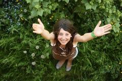 Het gelukkige meisje bevindt zich op een groen gras Stock Foto's