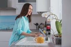 Het gelukkige meisje in de keuken wast een witte plaat voor het venster Stock Afbeeldingen