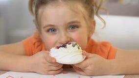 Het gelukkige meisje die smakelijke roomcake, ongezonde voeding, zwaarlijvigheidsrisico eten, sluit omhoog stock footage