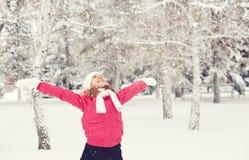 Het gelukkige meisje die van het leven genieten en werpt sneeuw in openlucht bij de winter Stock Afbeeldingen