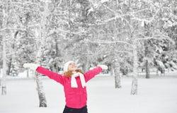 Het gelukkige meisje die van het leven genieten en werpt sneeuw in openlucht bij de winter Royalty-vrije Stock Fotografie