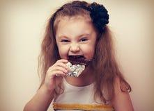 Het gelukkige meisje die van het pret glimlachende jonge geitje donkere chocolade met het hunkeren bijten naar ey Stock Foto