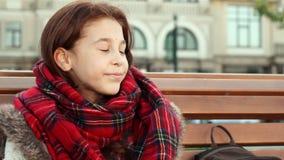 Het gelukkige meisje drinkt een warme drank terwijl het zitten op de straat stock footage