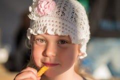 Het gelukkige meisje eet aardappel Stock Foto's