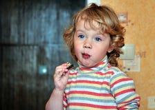 Het gelukkige meisje eet snoepjes Stock Foto's
