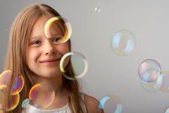 Het gelukkige meisje en de vliegende bellen Stock Afbeeldingen
