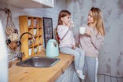 Het gelukkige meisje en haar mooie jonge moeder hebben samen ontbijt in een witte keuken Zij gieten en drinken thee moeder royalty-vrije stock foto