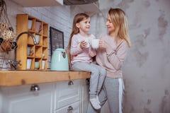 Het gelukkige meisje en haar mooie jonge moeder hebben samen ontbijt in een witte keuken Zij koesteren en drinken thee Moeder Zor royalty-vrije stock foto's