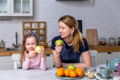 Het gelukkige meisje en haar mooie jonge moeder hebben samen ontbijt in een witte keuken Zij hebben pret en eten appelen royalty-vrije stock foto