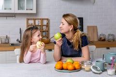 Het gelukkige meisje en haar mooie jonge moeder hebben samen ontbijt in een witte keuken Zij hebben pret en eten appelen royalty-vrije stock afbeeldingen