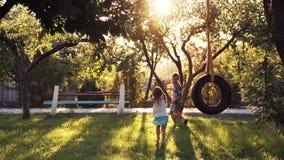 Het gelukkige meisje en jongens spelen bij park met schommeling stock videobeelden