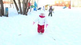 Het gelukkige meisje gaat en jongensspelen met schop op speelplaats bij de winter zonnige dag stock video
