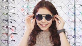 Het gelukkige meisje het glimlachen tonen beduimelt omhoog het dragen van zonnebril stock footage