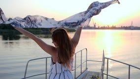 Het gelukkige meisje golven van kledij op aan boord van jacht aan rivier op achtergrondzonsondergang te winden stock videobeelden
