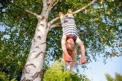 Het gelukkige meisje hangen van een boom in een de zomerpark royalty-vrije stock fotografie