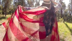 Het gelukkige meisje in hoed loopt met de vlag van de V.S. in de zomer, vreugde en geluk stock video