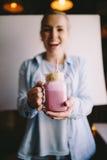 Het gelukkige meisje houdt de gestileerde kop van de metselaarkruik van roze koffie met heemst en decoratie Milkshake, cocktail E royalty-vrije stock foto's