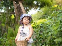 Het gelukkige meisje houdt de mand in het landbouwbedrijf De landbouw & Childre royalty-vrije stock afbeeldingen