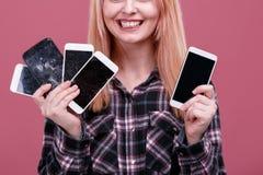 Het gelukkige meisje, houdt verscheidene smartphones en glimlacht Op een roze achtergrond Close-up Royalty-vrije Stock Afbeelding