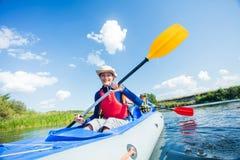 Het gelukkige meisje kayaking op de rivier op een zonnige dag tijdens de zomervakantie royalty-vrije stock afbeelding