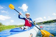 Het gelukkige meisje kayaking op de rivier op een zonnige dag tijdens de zomervakantie stock afbeelding