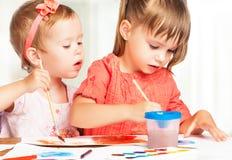 Het gelukkige meisje in kleuterschool trekt verven Stock Fotografie