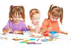 Het gelukkige meisje in kleuterschool trekt verven op witte achtergrond Royalty-vrije Stock Afbeelding