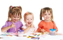 Het gelukkige meisje in kleuterschool trekt verven op witte achtergrond Royalty-vrije Stock Foto