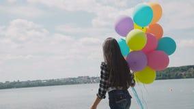 Het gelukkige meisje loopt en stelt met kleurrijke ballons op de kust van het meer stock video