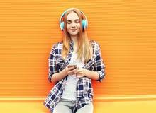 Het gelukkige meisje luistert en geniet van goede muziek in hoofdtelefoons Stock Foto
