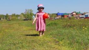 Het gelukkige meisje met bal gaat op groene weide dichtbij dorp stock videobeelden