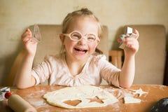 Het gelukkige meisje met Benedensyndroom bakt koekjes Stock Foto