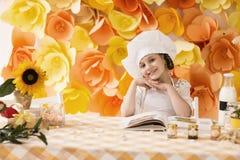 Het gelukkige meisje met boekchef-kok bereidt ontbijt voor die, die en voor de camera glimlachen stellen Stock Afbeeldingen