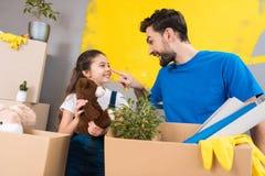 Het gelukkige meisje met doos van pluchespeelgoed bekijkt vader wat reparatie binnenshuis begon royalty-vrije stock afbeeldingen